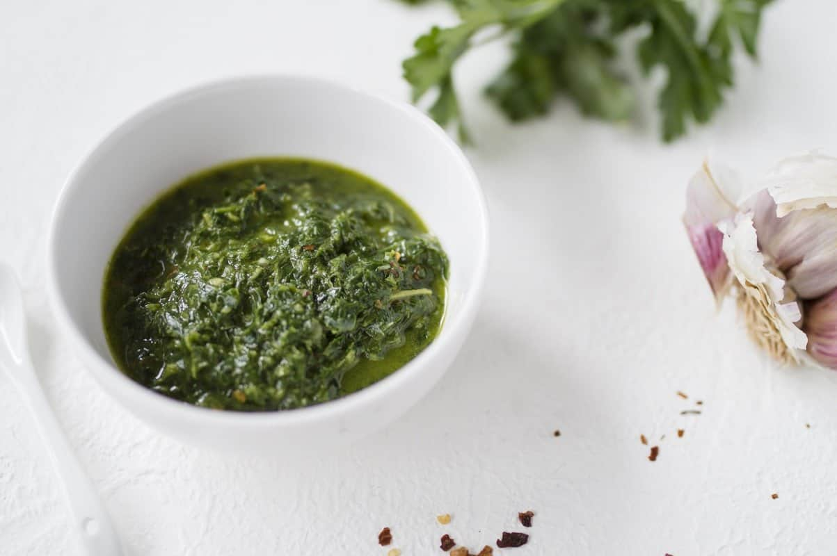 A dish of chimichurri - a green, herby Argentinian sauce