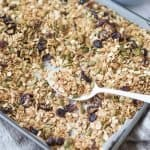 baking tray of nut free granola with white spoon resting on tray