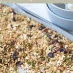 baking tray of nut free granola with white spoon resting on tray. Olive green background with text that reads nut free granola feel good eating