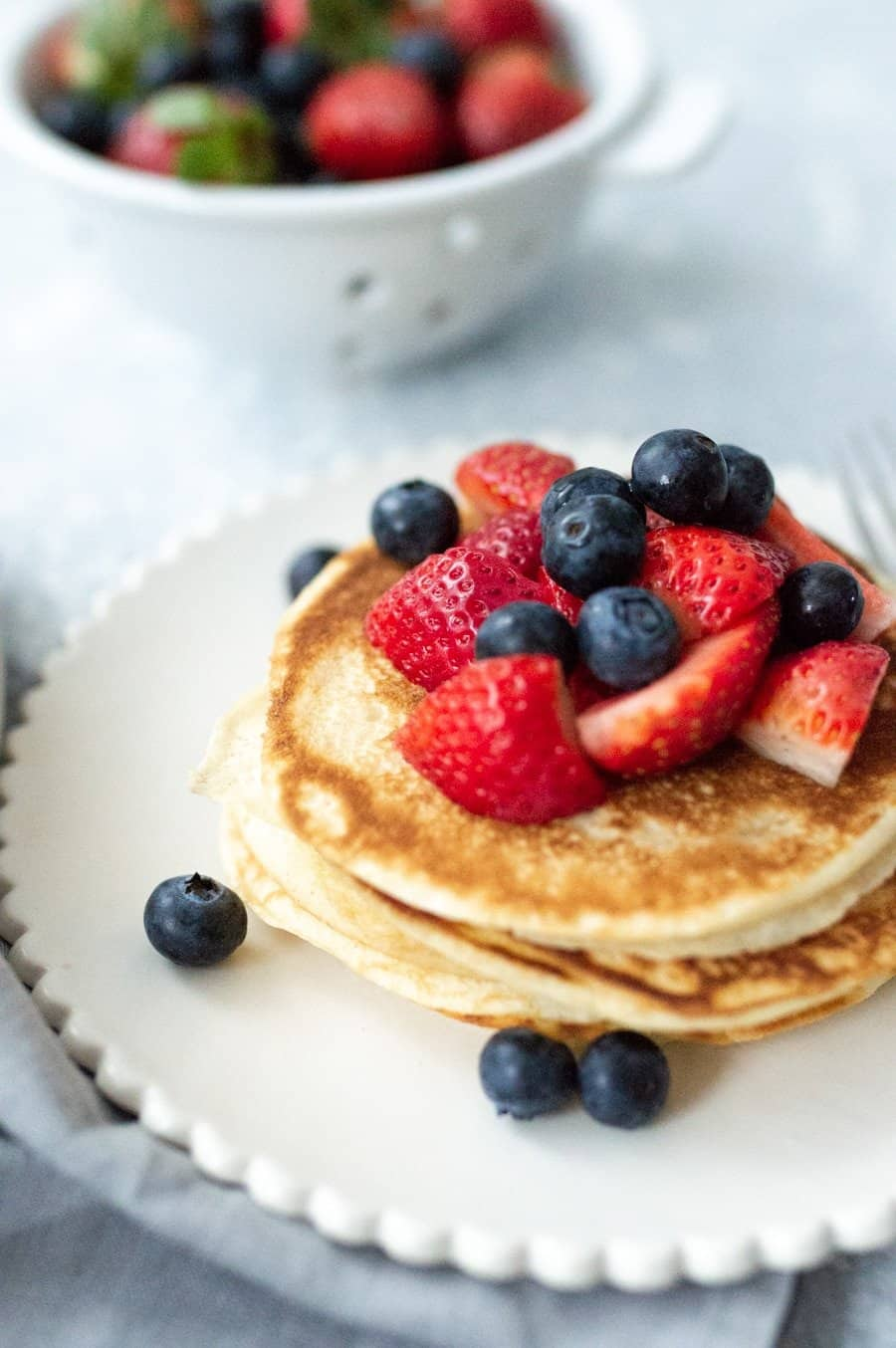 Scalloped plate with a stack of pancakes topped with strawberries and blueberries. In the background is a colander with more strawberries and blueberries