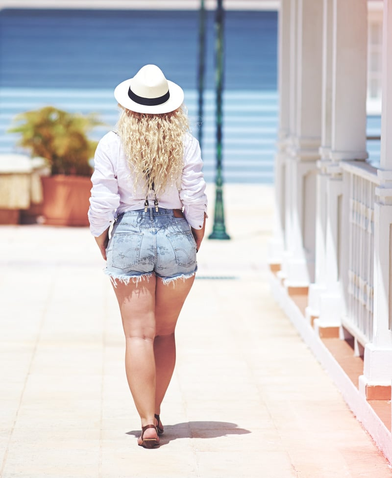 Rear view of woman in larger body in cutoff denim shorts, white shirt and fedora