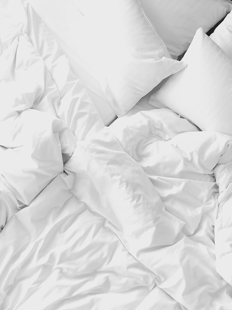 Unmade bed with white pillows and sheets