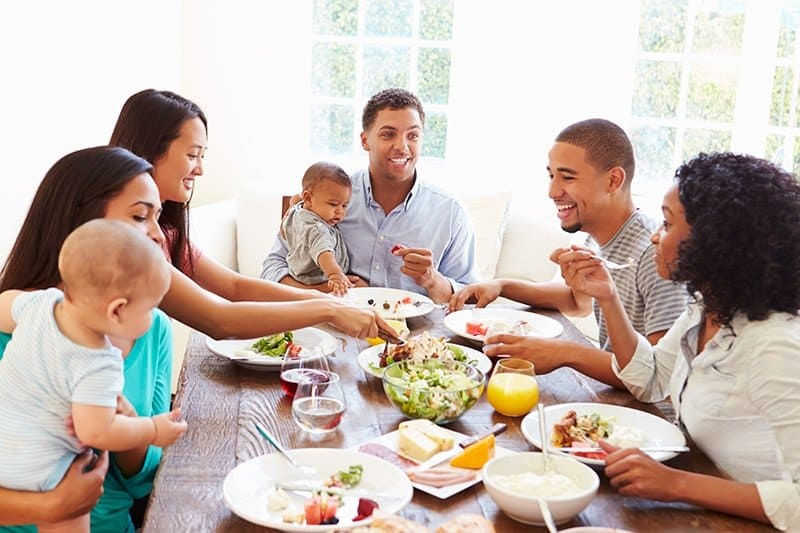 Adults and babies sitting around dining table enjoying a meal