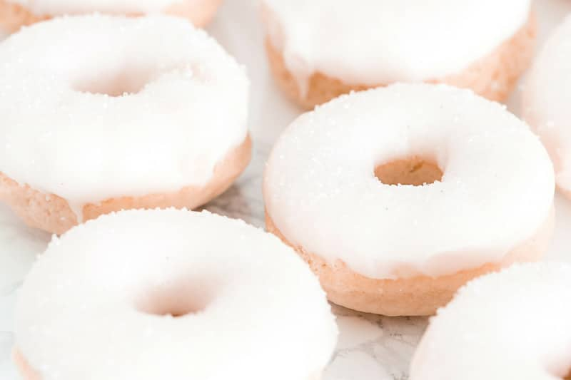 Six vanilla doughnuts with icing and sparkly sprinkles