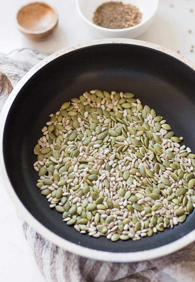 Fry pan with sunflower and pumpkin seeds in it that have been toasted to make nut free dukkah