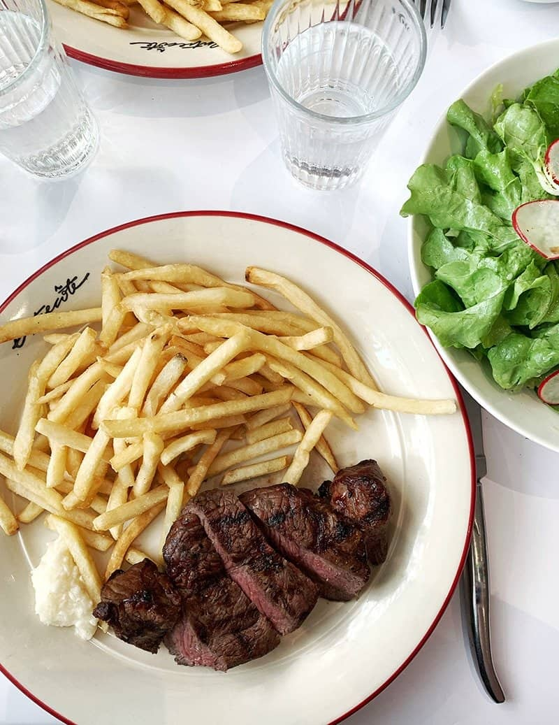 Sliced piece of medium cooked steak, French fries and horseradish on a white plate with red border. Off to the side is a white bowl with butter lettuce and radishes. There are glasses of water in the background