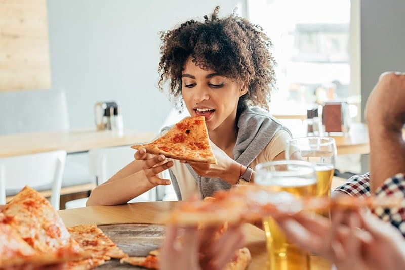 Woman of colour with curly hair about to bite into a slice of pizza