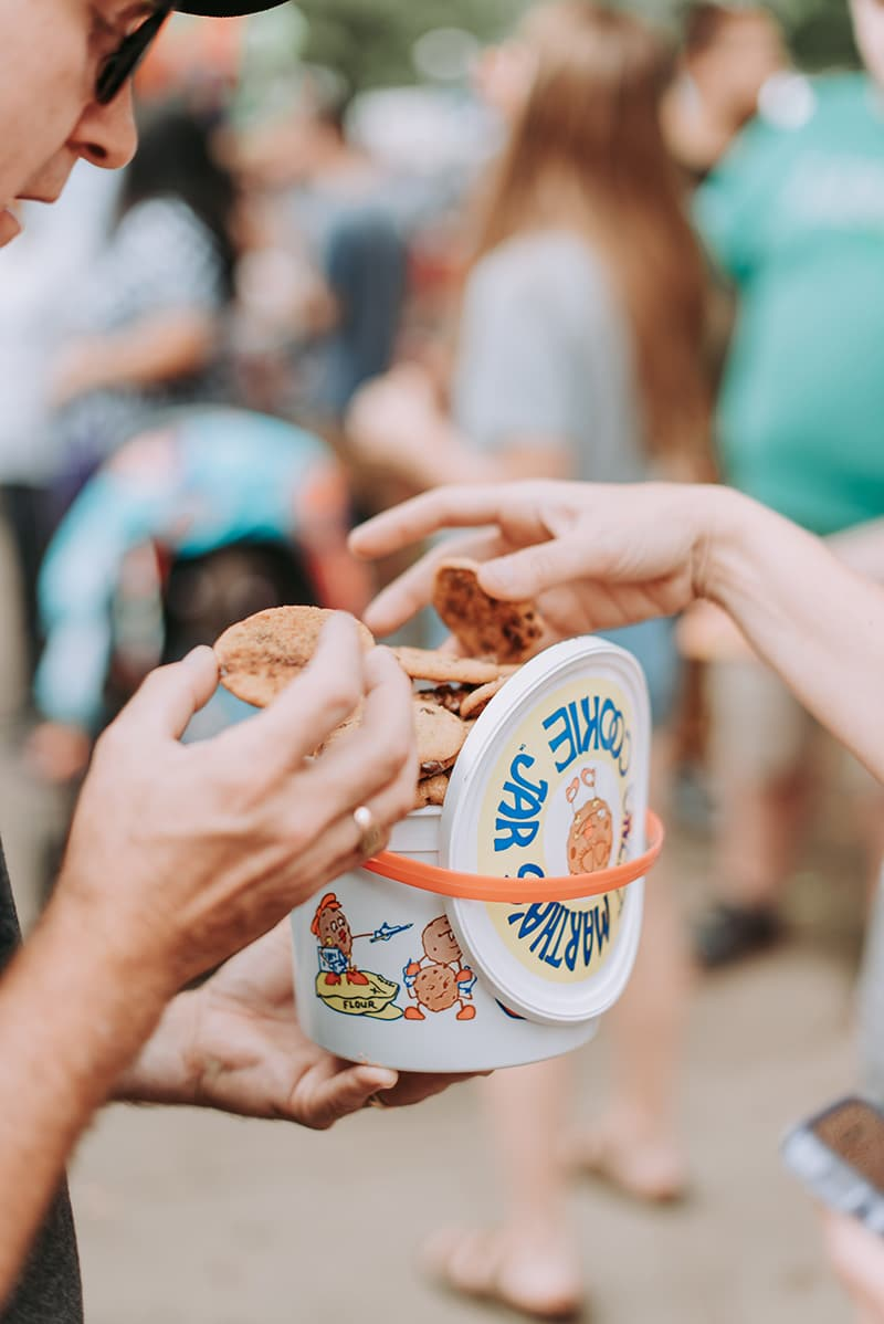 Crowd of people in background. In foreground is a tub of cookies with two hands reaching in to grab a cookie