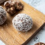 Wooden paddle with ceramic bowl containing rum balls. Rum balls scattered around