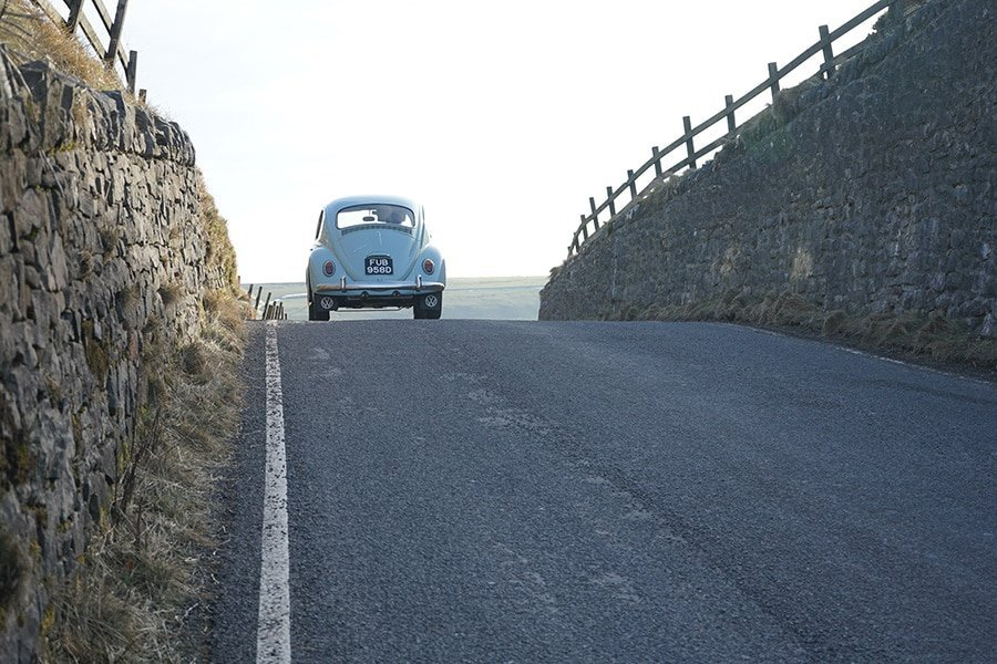 Light blue VW beetle driving on a road. The ocean is in the horizon