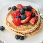 white scalloped edged plate with a stack of basic pancakes. Scattered over the pancakes are blueberries and sliced strawberries.