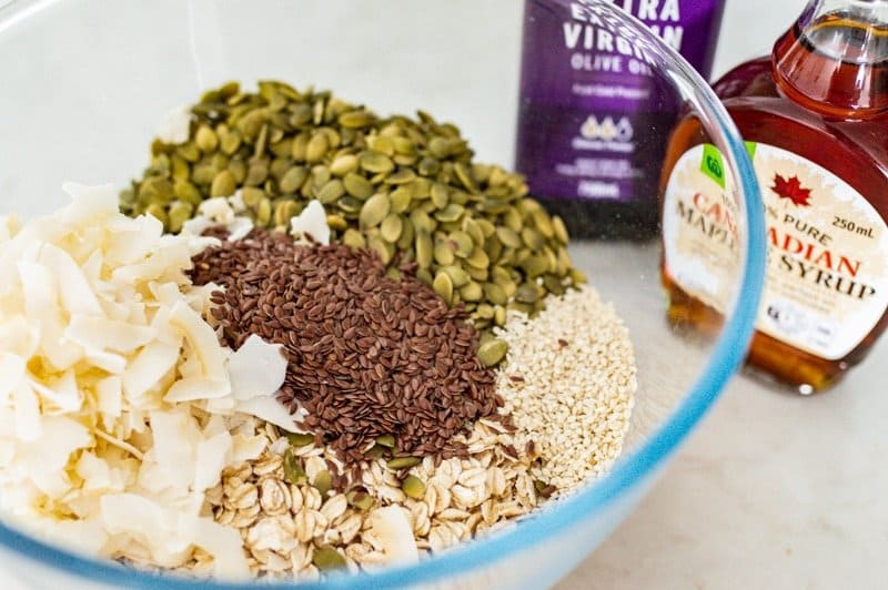 Glass bowl filled with nut free granola ingredients: oats, pumpkin seeds, coconut flakes, sesame seeds and flax seeds. In the background is a bottle of extra virgin olive oil and a bottle of maple syrup.