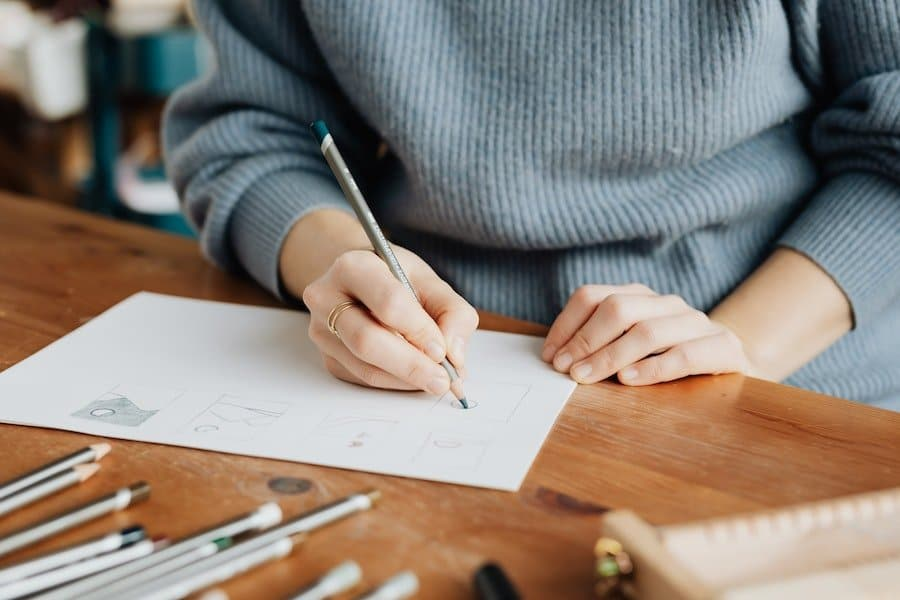 A person in a grey ribbed jumper is sketching. This type of activity can provide a distraction after a binge.