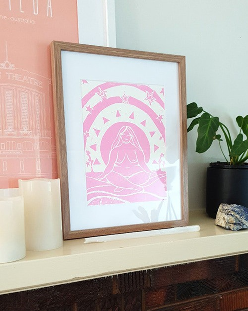 A hand printed image of a fat female-looking human surrounded by abstract shapes. The print is in pink ink and is in a light coloured wooden frame on a mantle.