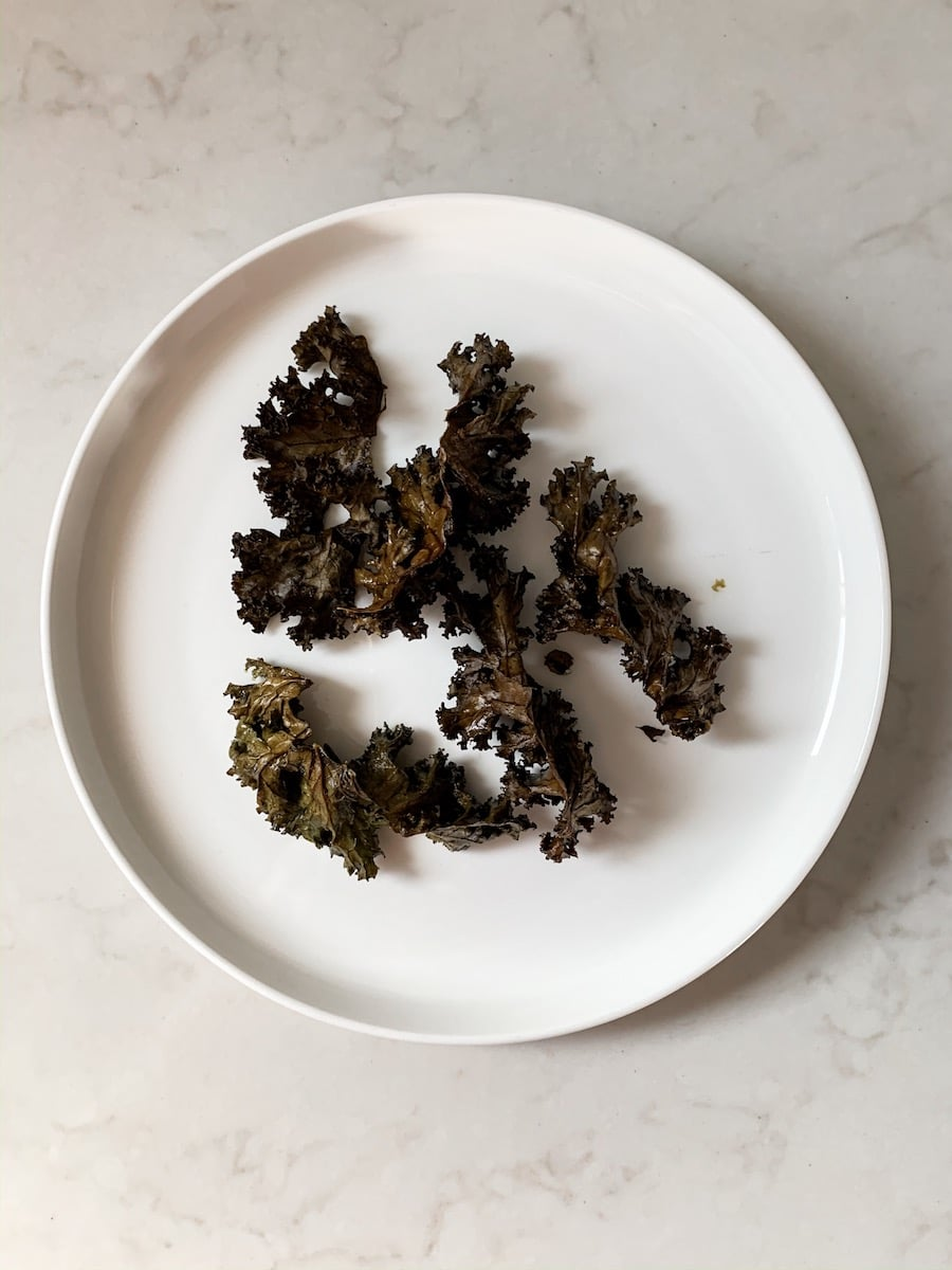 A plate of burnt kale chips on a bench.