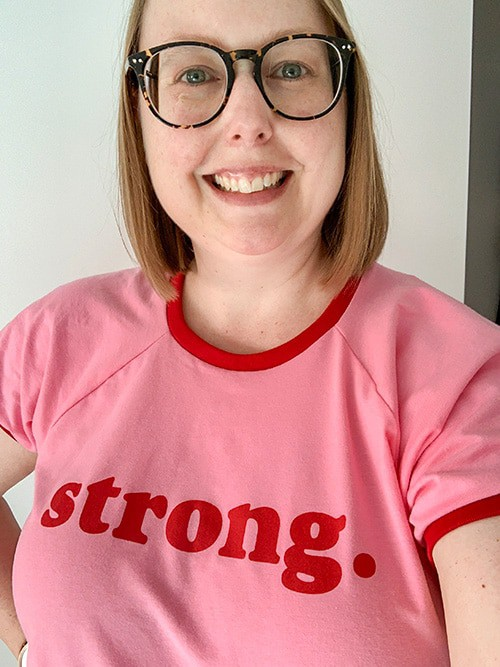 A smiling woman with shoulder length dark blonde hair and big round glasses. She wears a bright pink and red t-shirt that reads Strong.