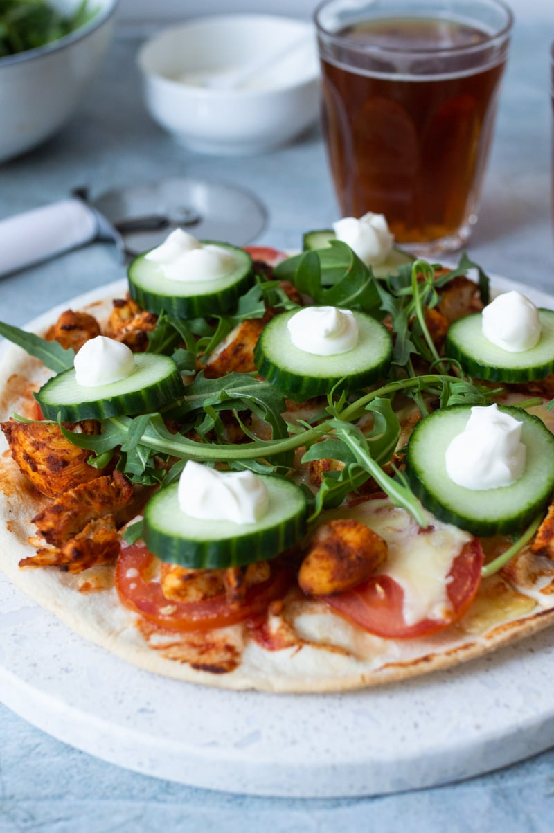 Tandoori chicken pizza on a stone serving board