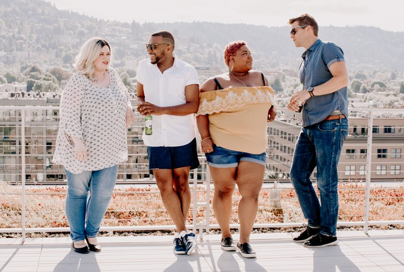 A white female-passing person in a large body talking to a male-passing POC. Next to him is a short large bodied POC talking to a tall caucasian male