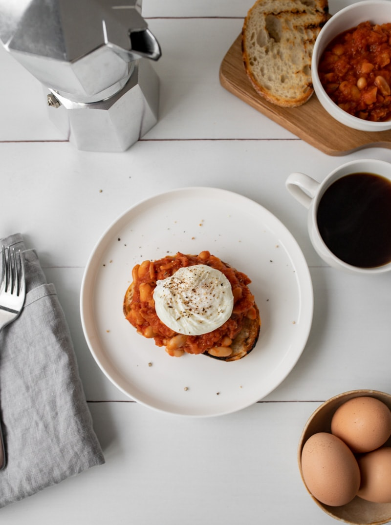 A plate with a piece of toast topped with smoky baked beans and a poached egg. There is a cup of coffee, espresso pot, eggs and tea towel in the background