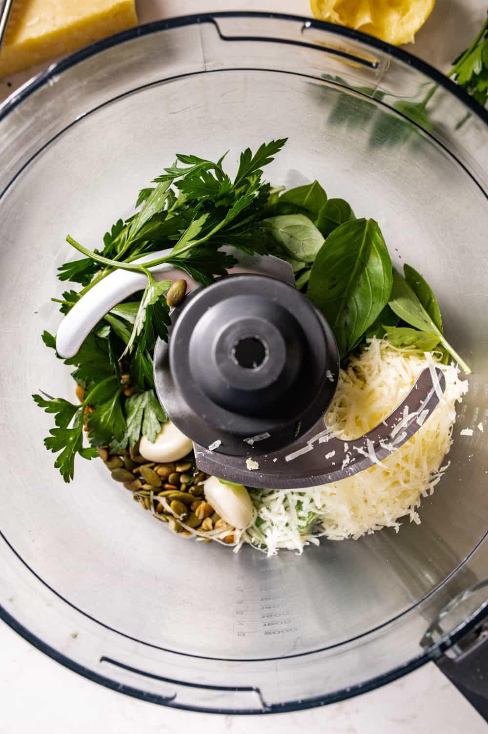 Overhead shot of nut-free pesto ingredients in a food processor